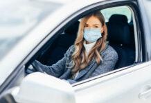 Eine junge Frau mit Schutzmaske im Auto