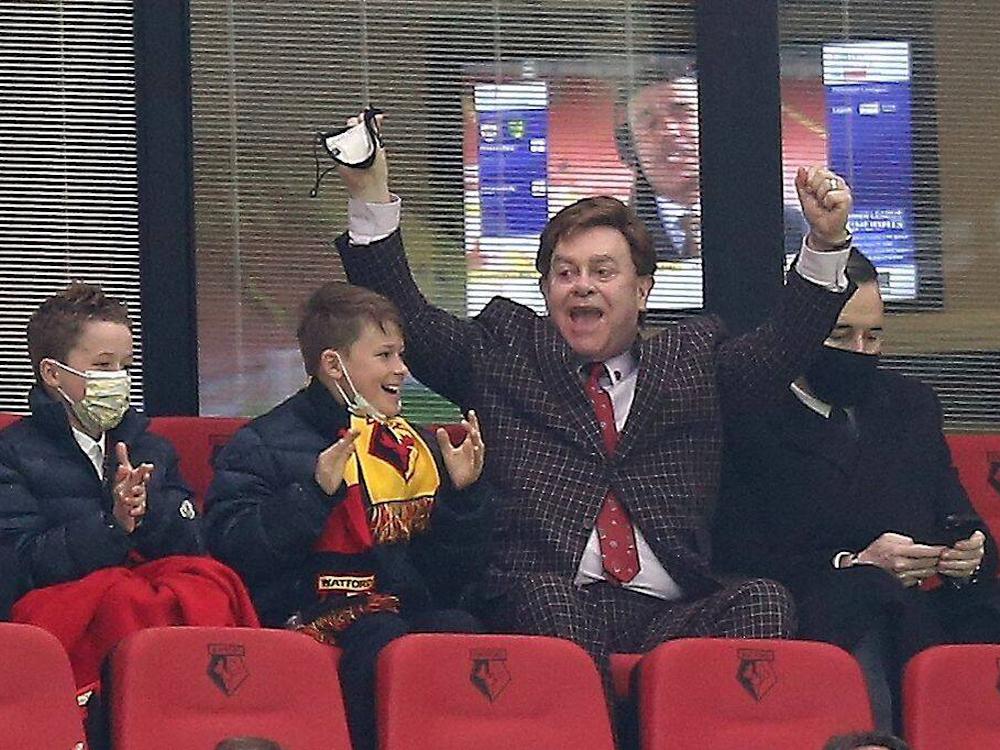 Edelfan-Elton-John-jubelt-im-Fussballstadion-mit-Anzug-und-Krawatte